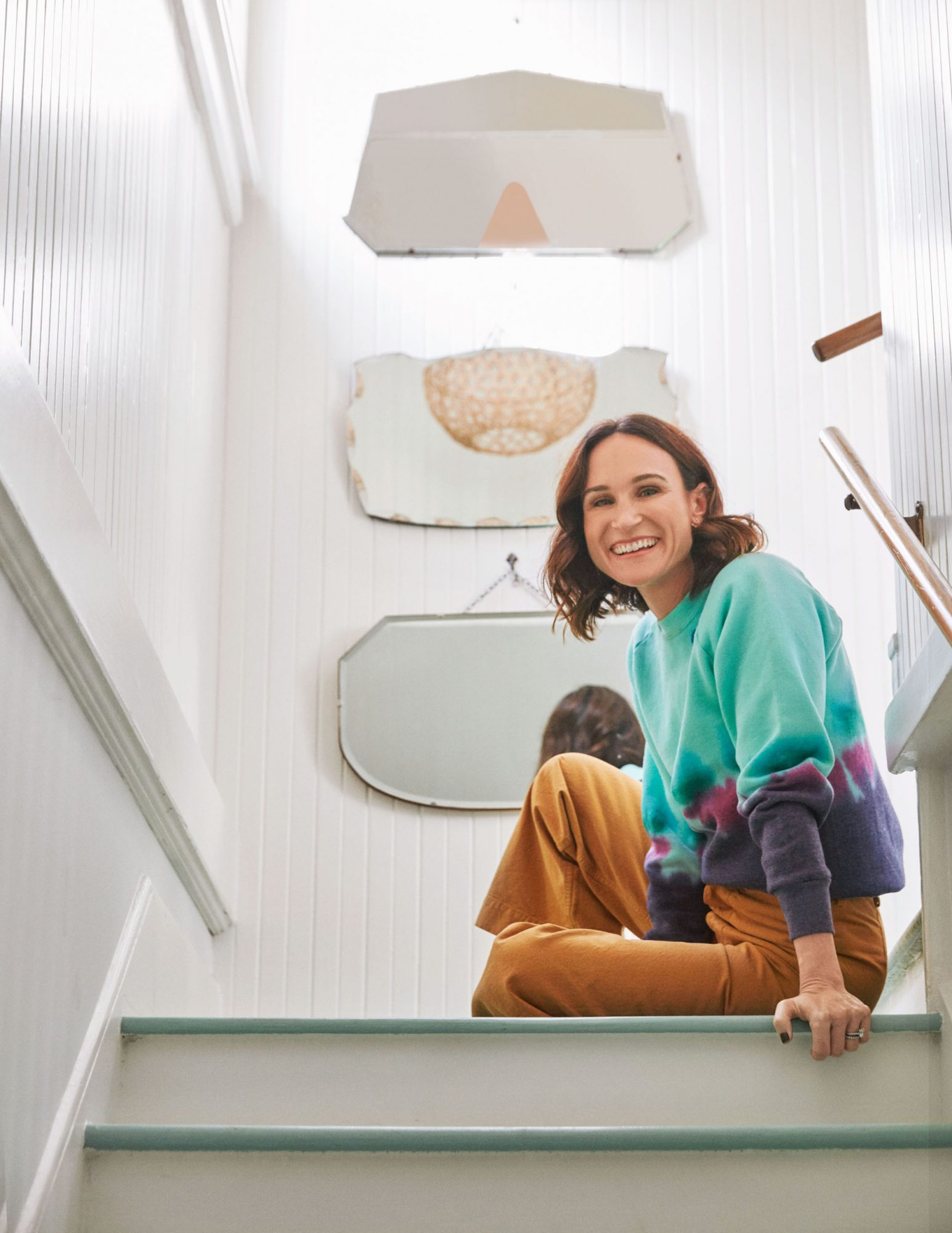 melissa akkaway sitting on pastel-painted staircase