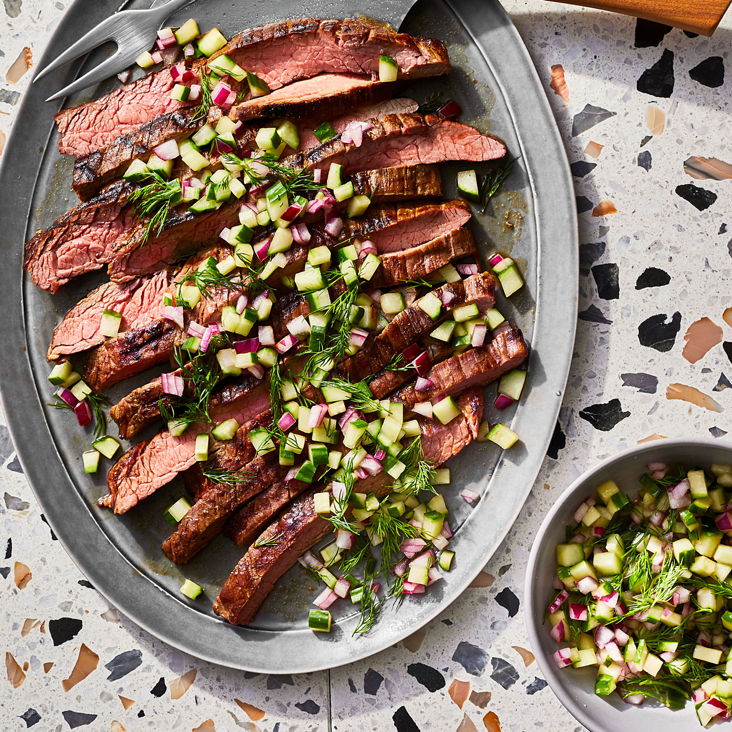 plate of Grilled Flank Steak with bowl of Cucumber-Dill Salsa