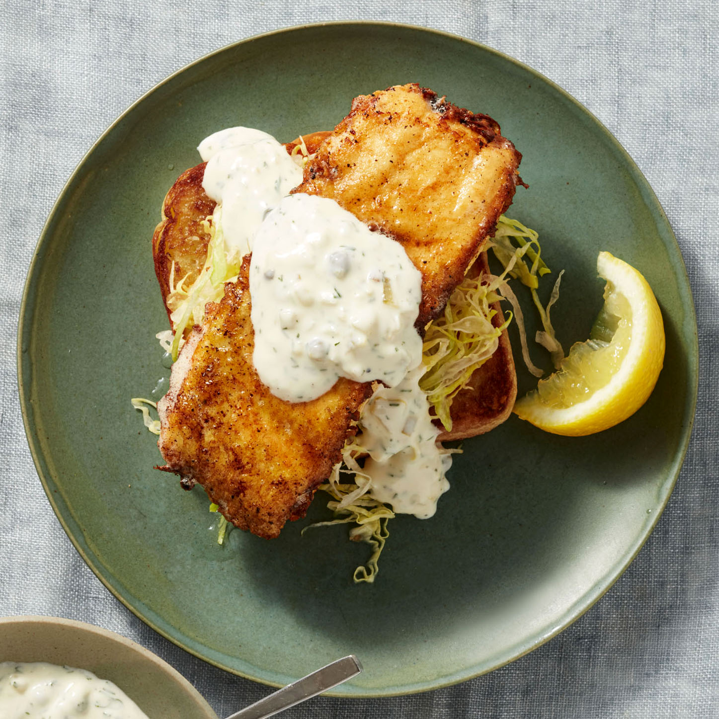 Egg-Battered Fishwiches on Toast with Yogurt Tartar Sauce served with a lemon wedge