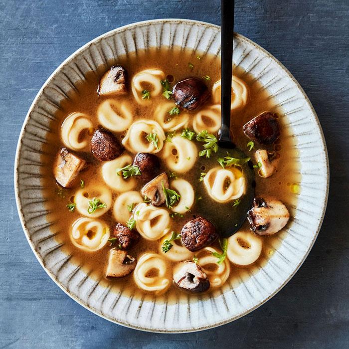 tortellini en brodo with mushrooms in grey bowl