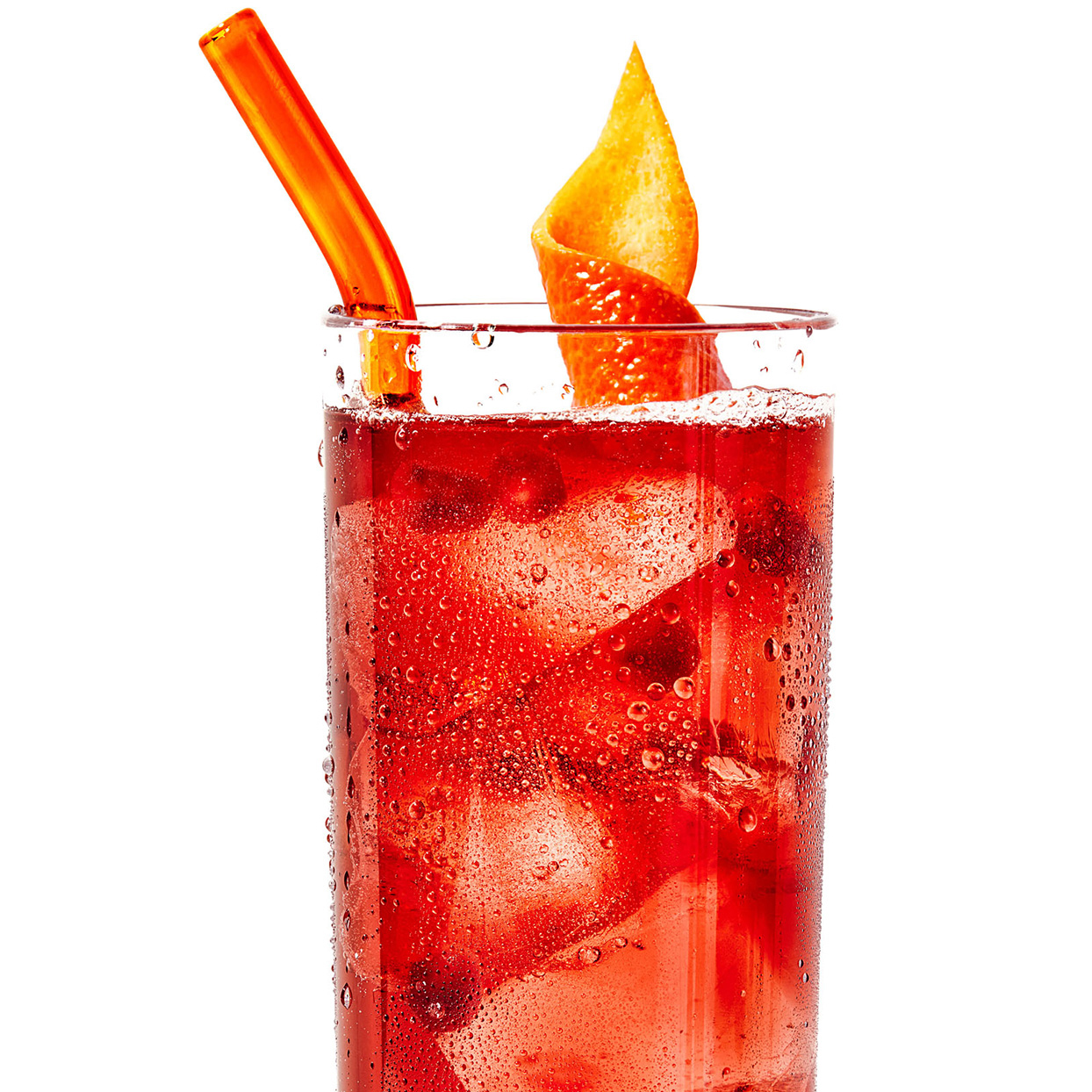 red harvest moon cocktail drink with orange peel and straw