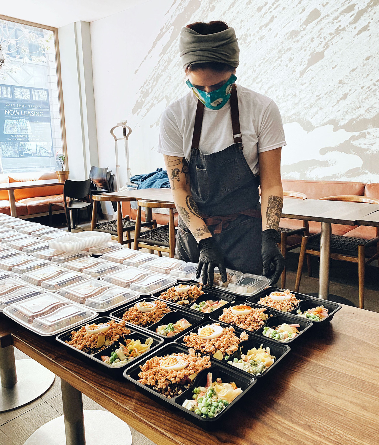worker placing lids on food trays