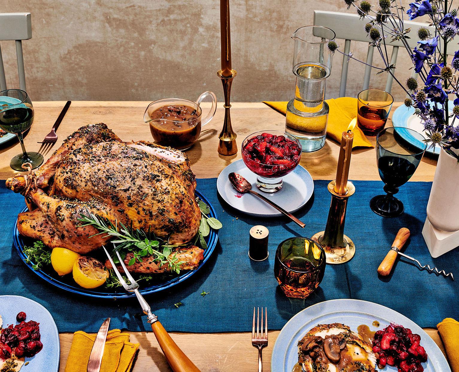 holiday table with roast turkey, gravy, blue table runner, candles, and dried florals