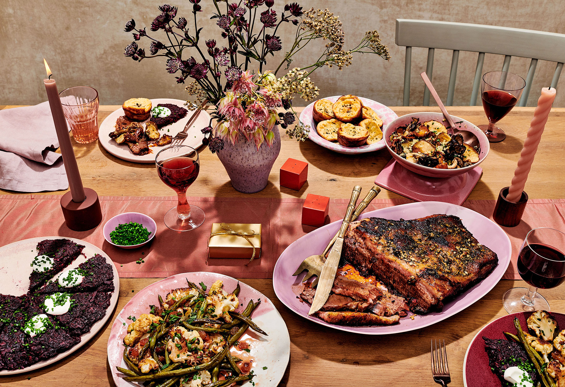 wood table with rust-colored runner, dried floral arrangement, and holiday food