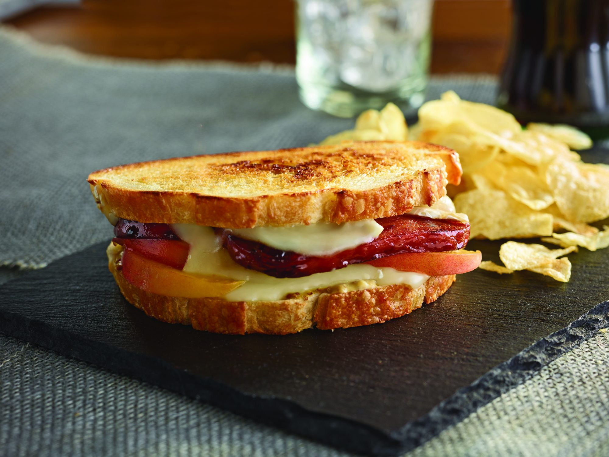 Spam with Brie and Peaches grilled cheese sandwich with potato chips.