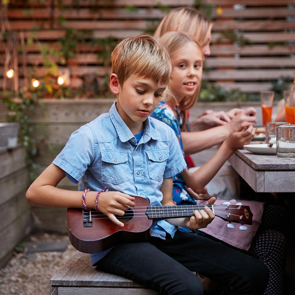 boy playing ukulele summer party