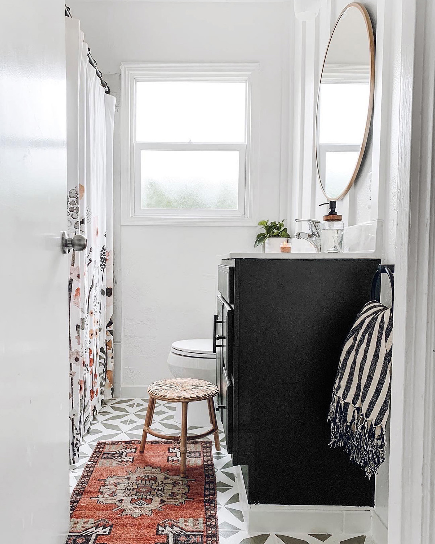 narrow white bathroom with black vanity
