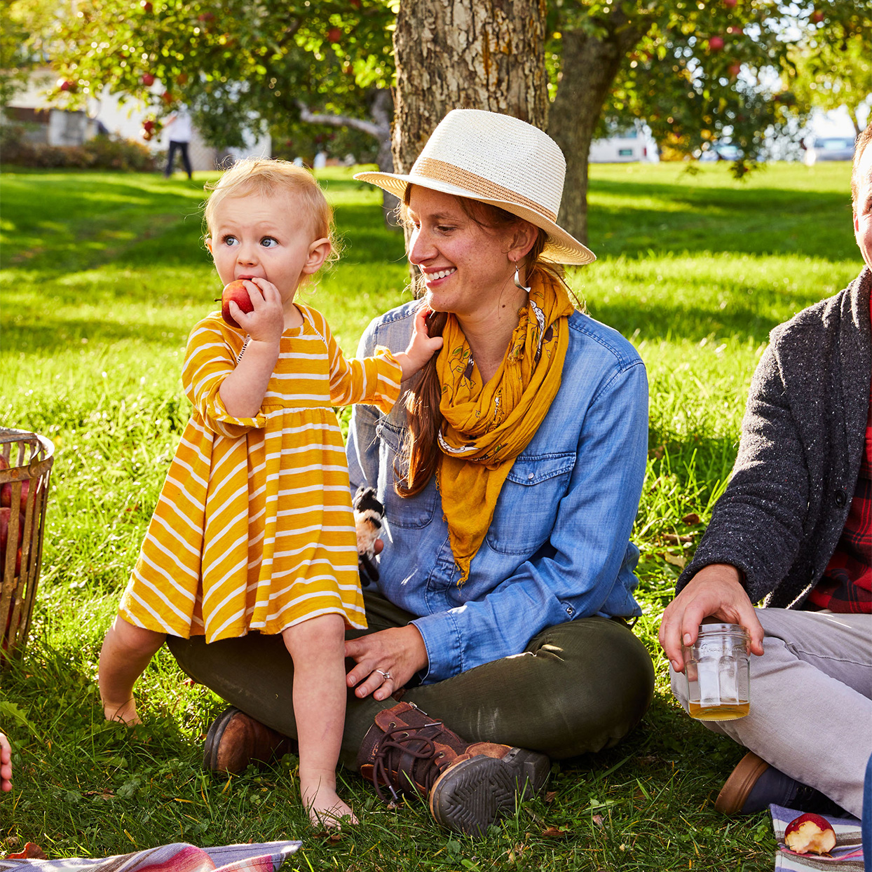 little girl with mom eating apple at picnic