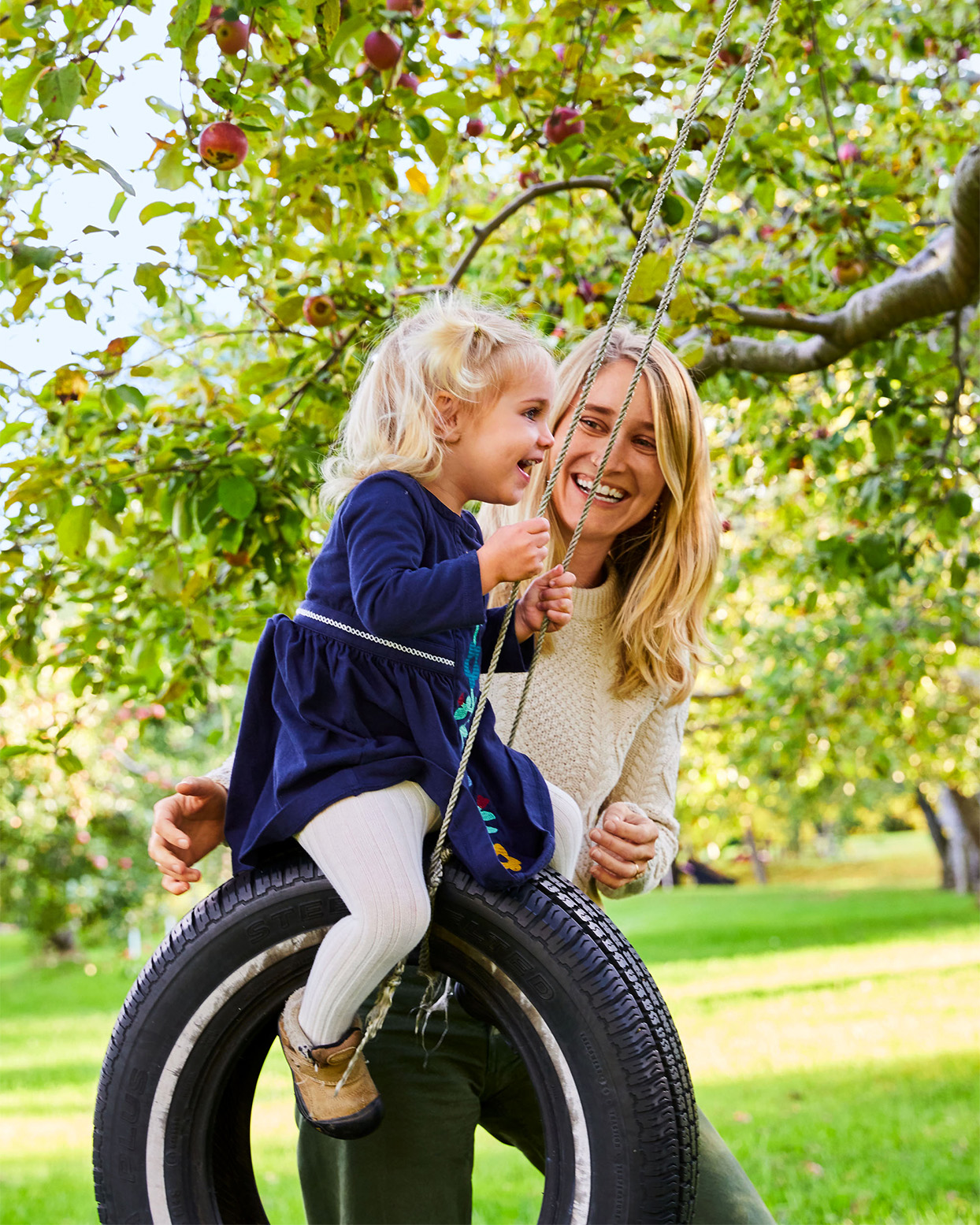 little girl and mom on tire swing