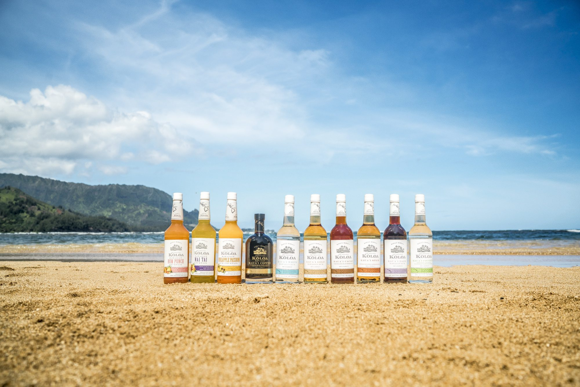 Koloa's line of rums and bottled cocktails lined up on a beach