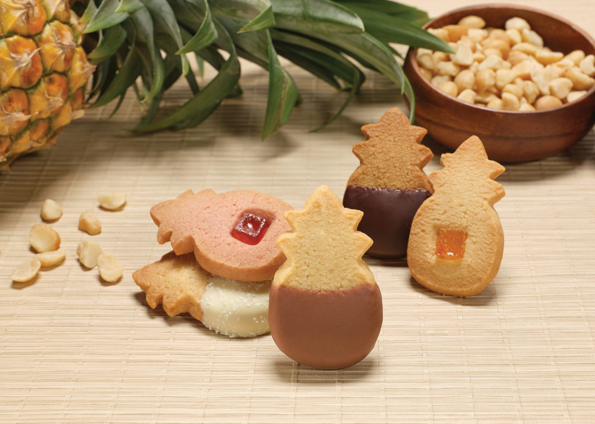 Assortment of cookies in front of a pineapple and macadamia nuts