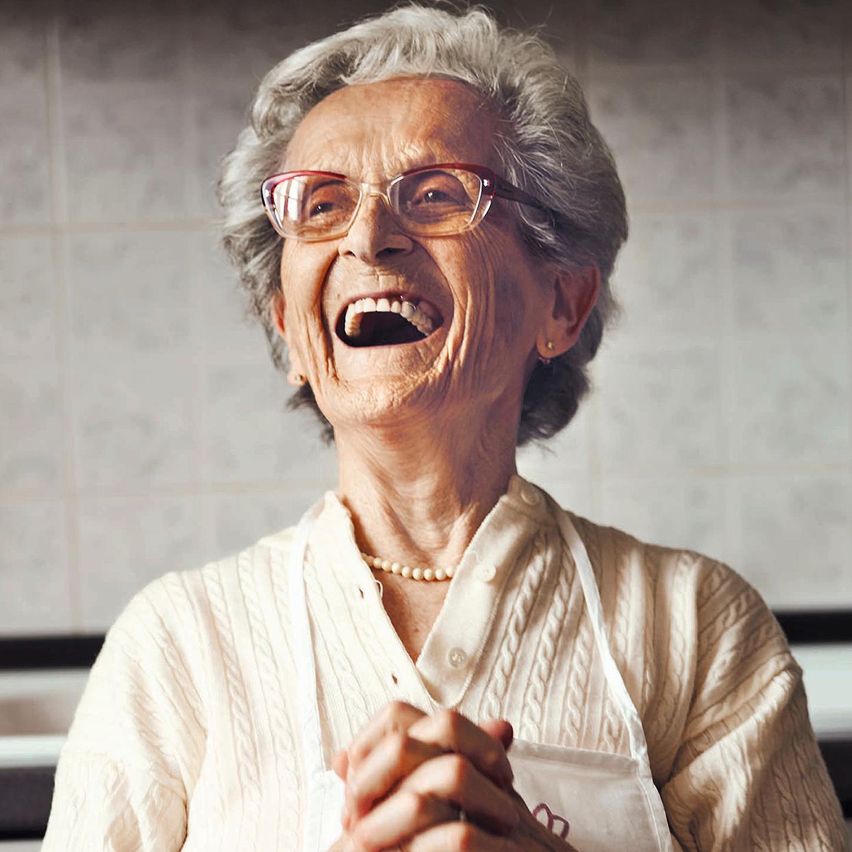 elderly woman smile pearl necklace cat-eye glasses apron kitchen