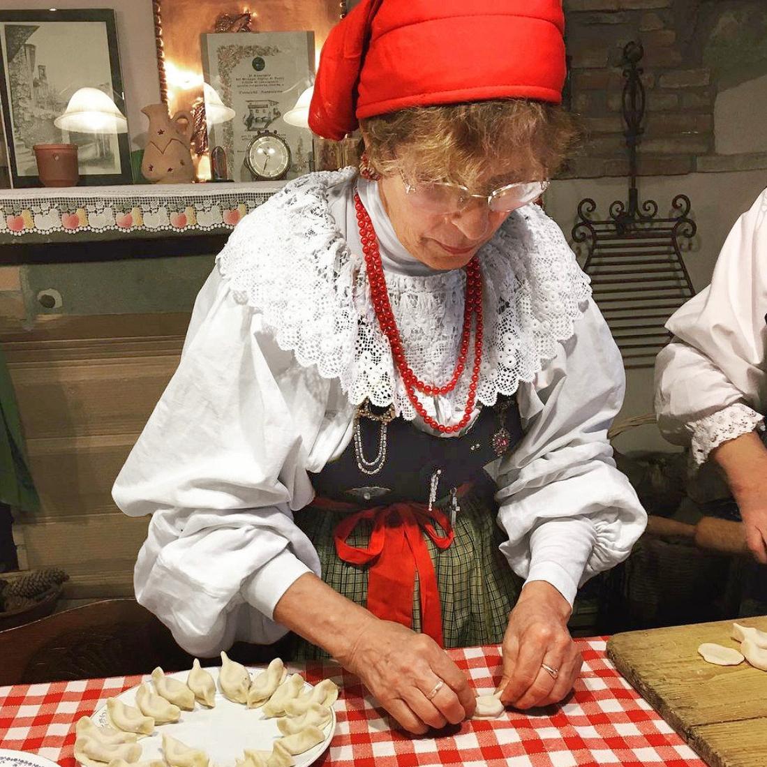 older woman traditional dirndl dress hat preparing dumplings