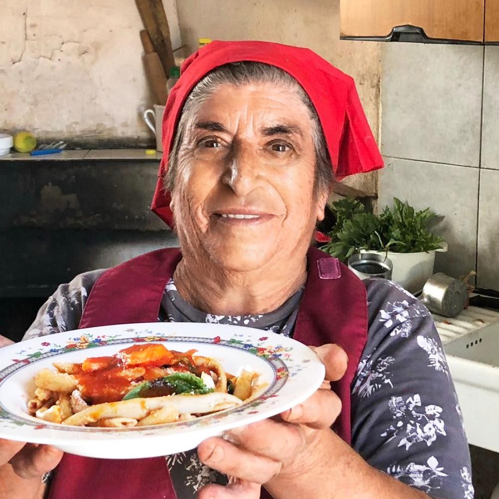 older Italian woman red head scarf pasta dish kitchen
