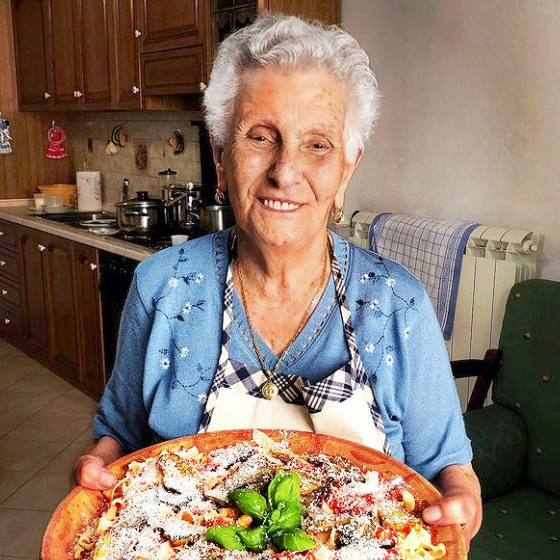 elderly woman kitchen pasta dish blue blouse apron