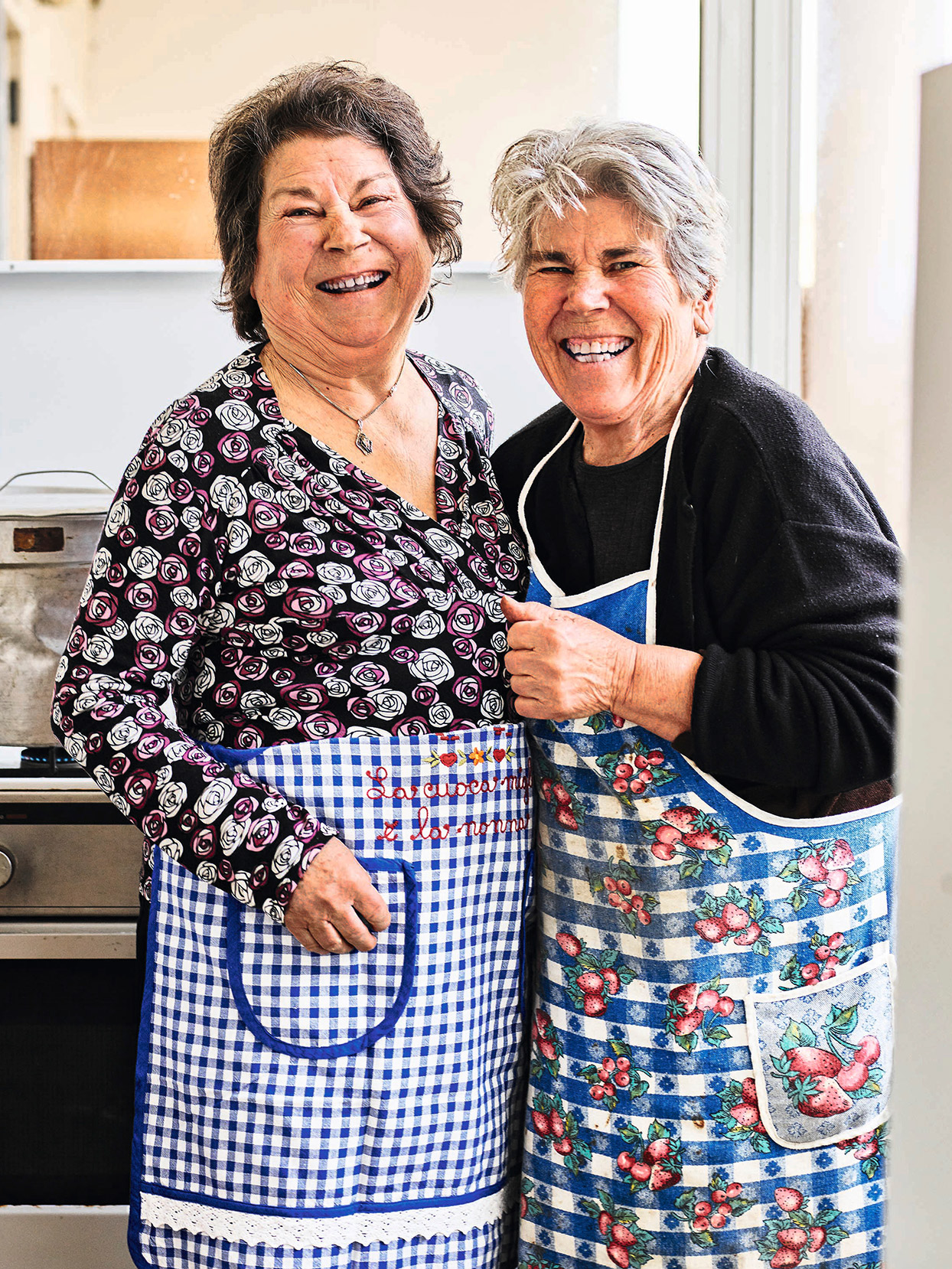 two older Italian women kitchen smiles frilly blue aprons