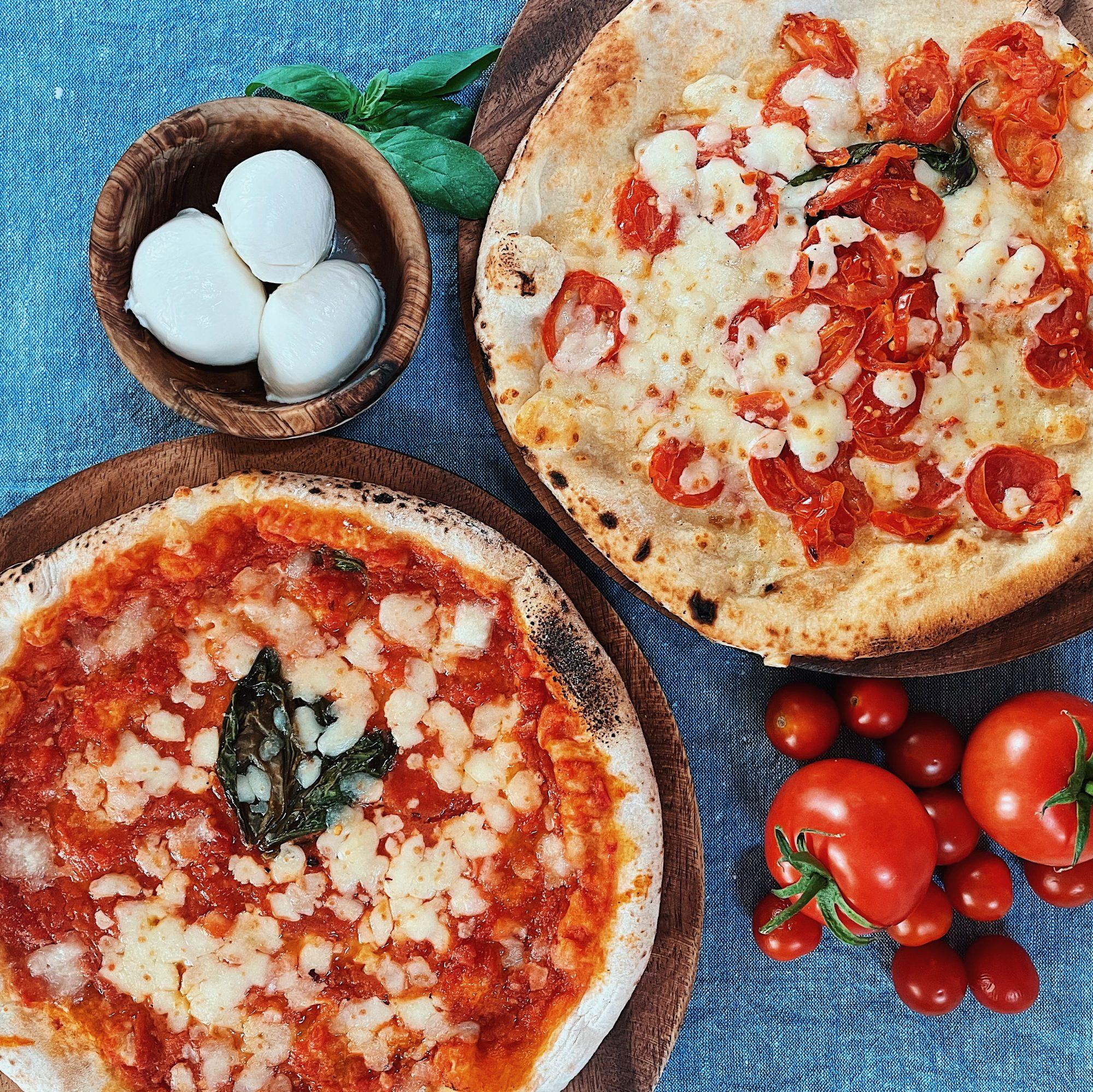 Two round Talia di Napoli pizza pies