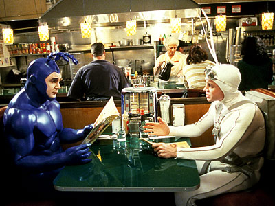 The Tick, Patrick Warburton | (1994-1997, Fox) Premise: A big, blue nigh-invulnerable lunkhead named the Tick patrols the City, battling villains like El Seed, Chairface Chippendale, and the Breadmaster, and…