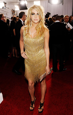Kesha   KE$HA The hair and makeup may be Ke$ha's signature garbage-chic, but the gold flapper mini by Nicolas Jebron looked more sloppy Vegas showgirl. Grade: D-