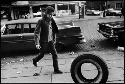 Bob Dylan | BOB DYLAN (1963) How many roads did Dylan walk down before Marshall took this shot of the legendary singer-songwriter kicking a tire in New York?…