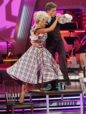 Dancing with the Stars | PAMELA ANDERSON AND DAMIAN WHITEWOOD: QUICKSTEP Pam's 9 to 5 -inspired dress was so buttoned-up, she had to dance atop a table to get attention.