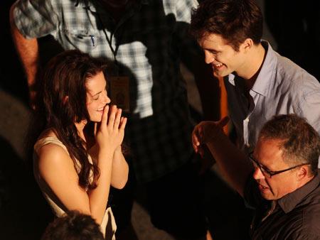 Kristen Stewart, Robert Pattinson | Stewart and Pattinson have a laugh between takes with director Bill Condon.