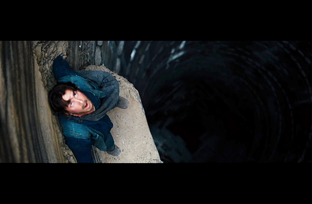 The Dark Knight Rises   Is this Bruce Wayne escaping from captivity? Or does this scene take place earlier in the movie? Bale's look here is very similar to his…