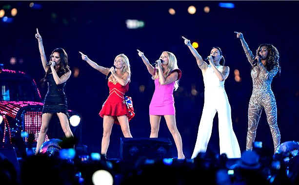 Spice Girls, Summer Olympics 2012 | Victoria Beckham (in a custom Gilles Deacon little black dress), Geri Halliwell (in a red dress with Union Jack bustle by Susan Neville), Emma Bunton…
