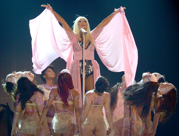 A defiant Xtina infused her performance with a positive message, sharing the stage with a collection of supposed ''freaks'' and ''losers'' for an empowering Lotus…