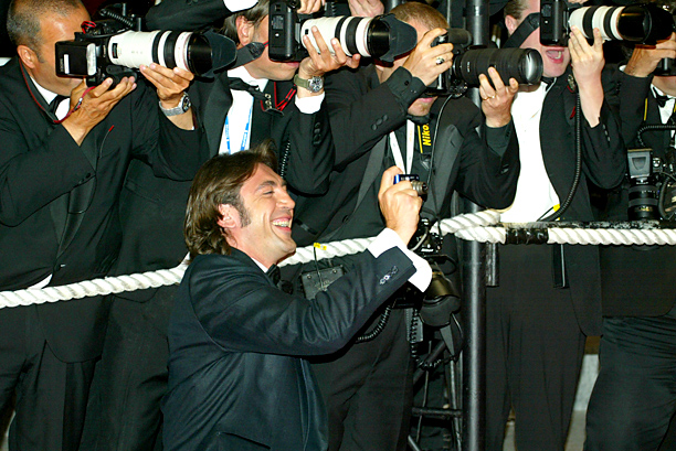 Javier Bardem kneels by press photographers to take a picture of his fellow jury members