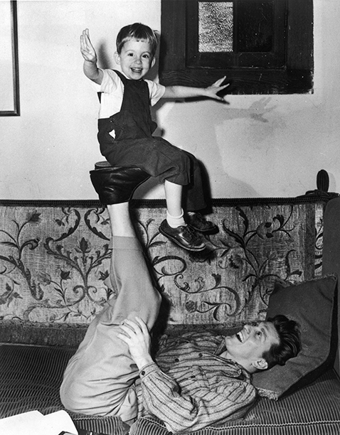 GALLERY: Kirk Douglas Through the Years: GettyImages-3172566.jpg 1948: American actor Kirk Douglas lying on a couch with his legs in the air as he balances his son, Michael on the soles of his feet.
