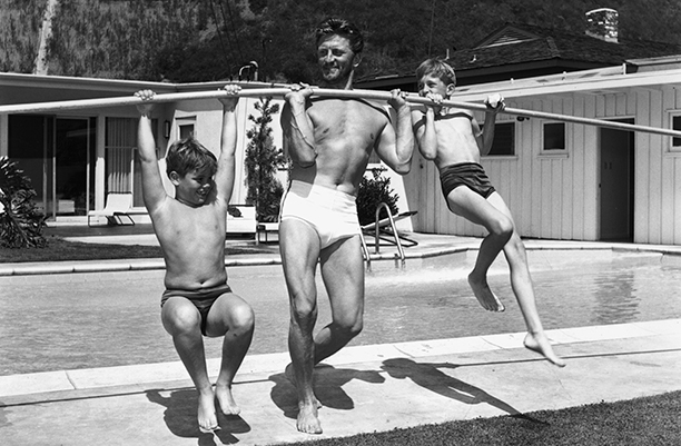 GALLERY: Kirk Douglas Through the Years: GettyImages-3209341.jpg circa 1955: Full-length image of American actor Kirk Douglas using a pole to lift his sons, Joel (L) and Michael, on the deck of a swimming pool.