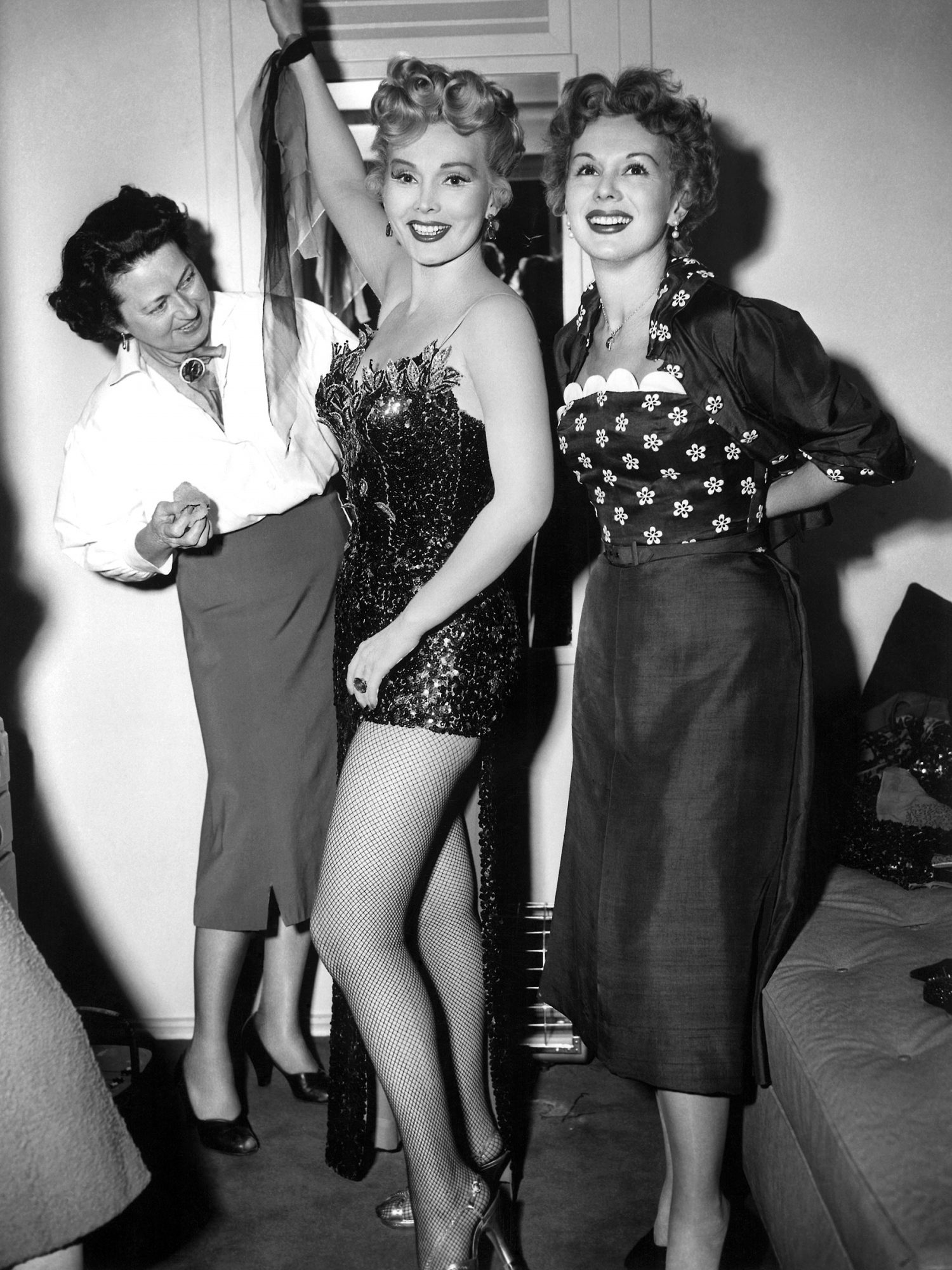 LILI, from left: Edith Wilson applies body makeup to Zsa Zsa Gabor while sister Eva Gabor visits in