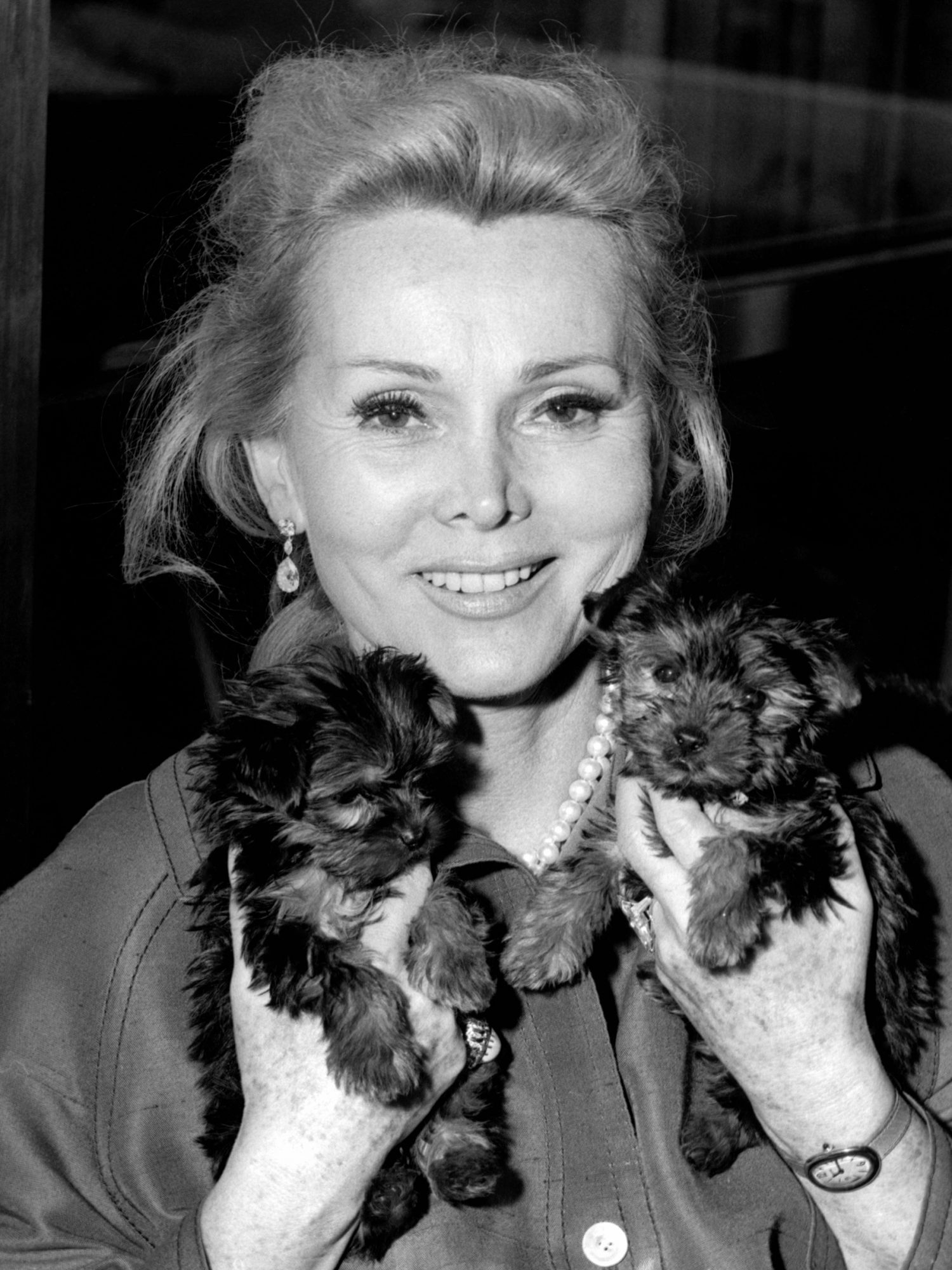 Zsa Zsa Gabor cuddling with her two terriers, Zsa Zsa and Eva Super-Duper, 1968