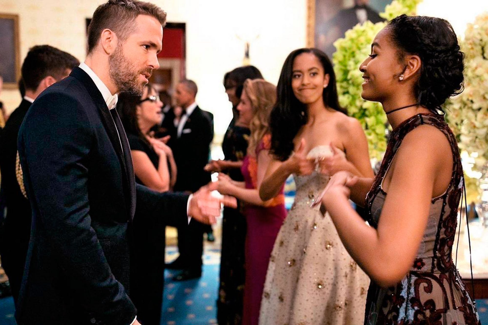 Malia Obama's thumbs up as her sister Sasha talks to Ryan Reynolds at the White house. March 10, 2016 Official White House Photo by Pete Zouza Rights: This official White House photograph is being made available only for publication by news organizations and/or for personal use printing by the subject(s) of the photograph. The photograph may not be manipulated in any way and may not be used in commercial or political materials, advertisements, emails, products, promotions that in any way suggests approval or endorsement of the President, the First Family, or the White House.