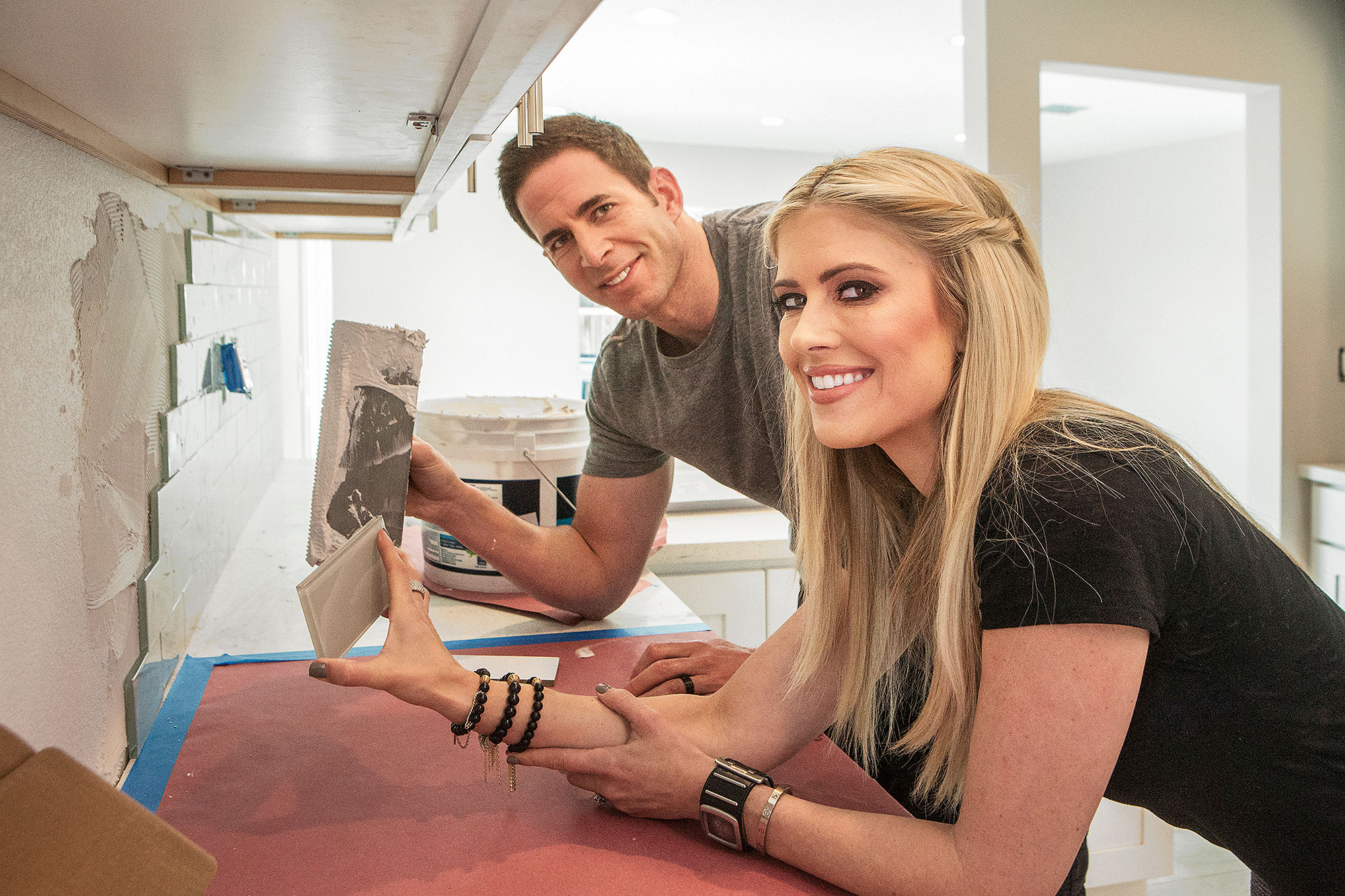 As seen on HGTV's Flip or Flop, Tarek and Christina El Moussa install back-splash tiles in the kitchen of a home that they are renovating. © 2015, HGTV/Scripps Networks, L.L.C. All Rights Reserved Commissioned photographer