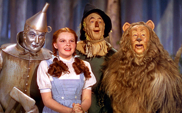 'The Wizard of Oz ' - Bert Lahr puts tomato can sticker all over Jack Haley's Tin Man costume