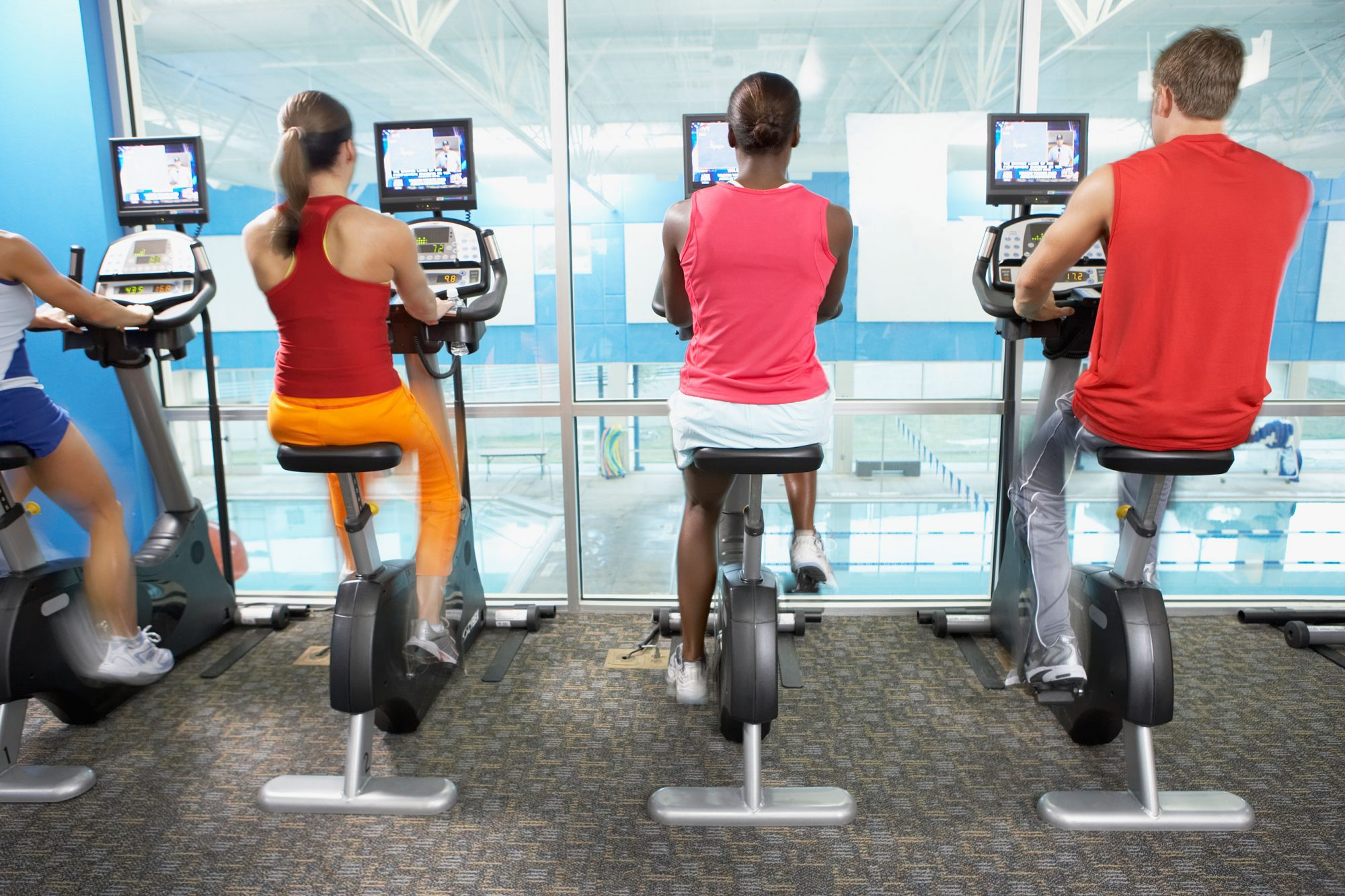 Men and women on cycling machines