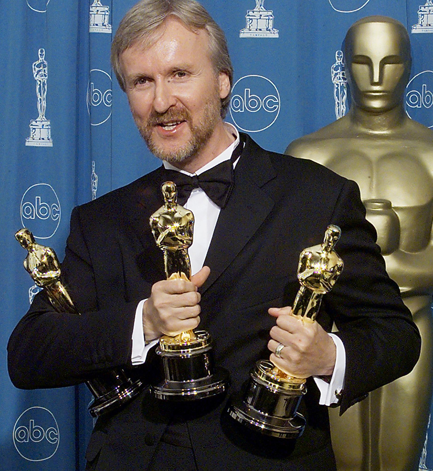 James Cameron holds the three Oscars he won for Be