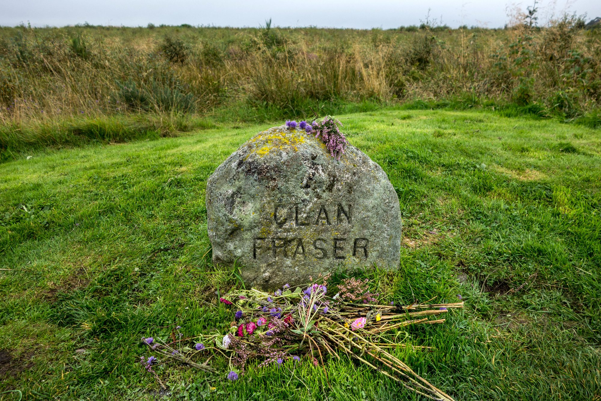 Flowers at headstone that marks the mass grave of fallen Jacobite soldiers of the clan Fraser.