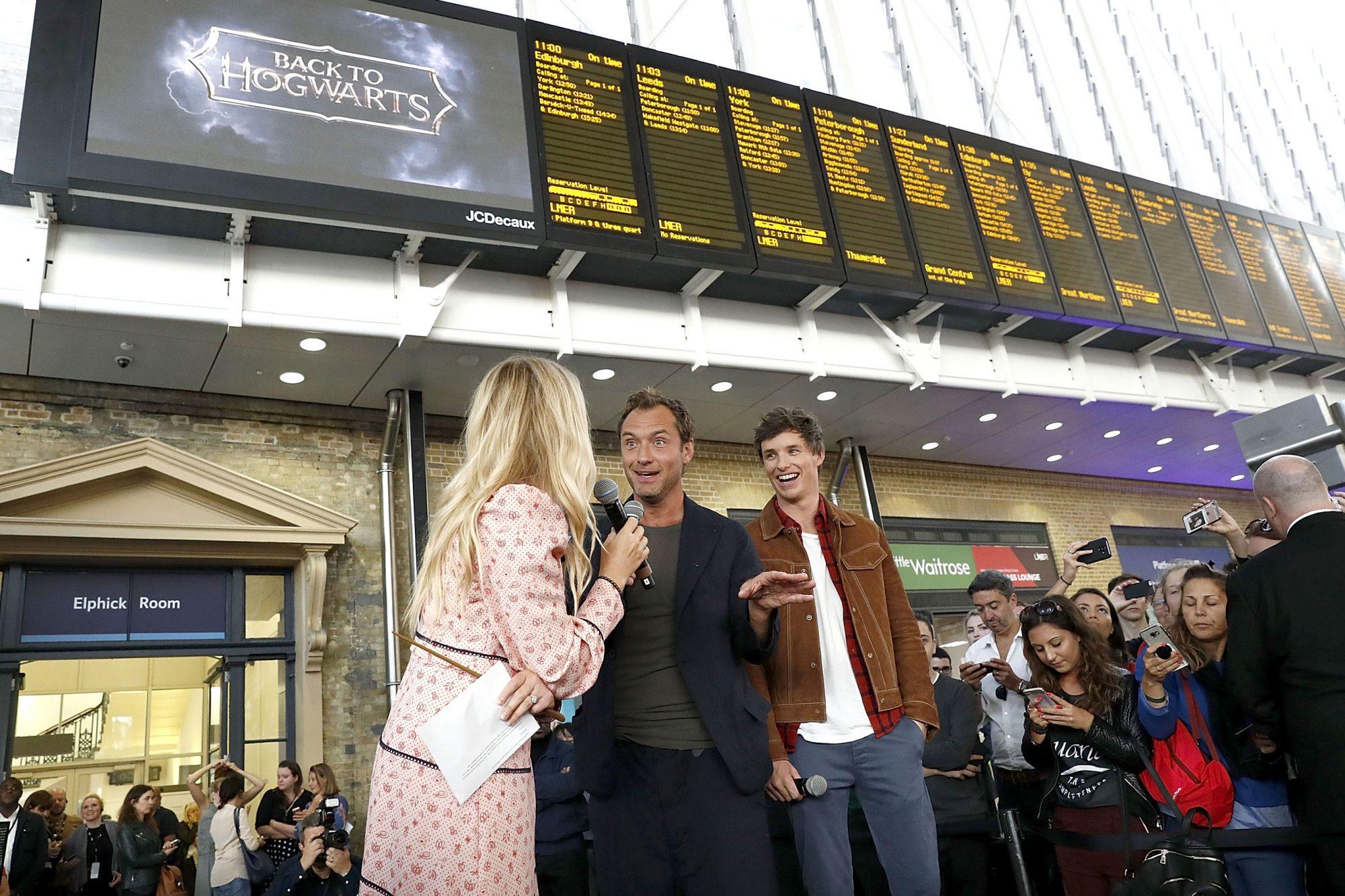 LONDON, ENGLAND - SEPTEMBER 01: Eddie Redmayne (R) and Jude Law (L), stars of Fantastic Beasts: The Crimes Of Grindelwald, surprise fans at platform 9 3/4 during 'Back to Hogwarts' day celebration at Kings Cross Station on September 1, 2018 in London, England.