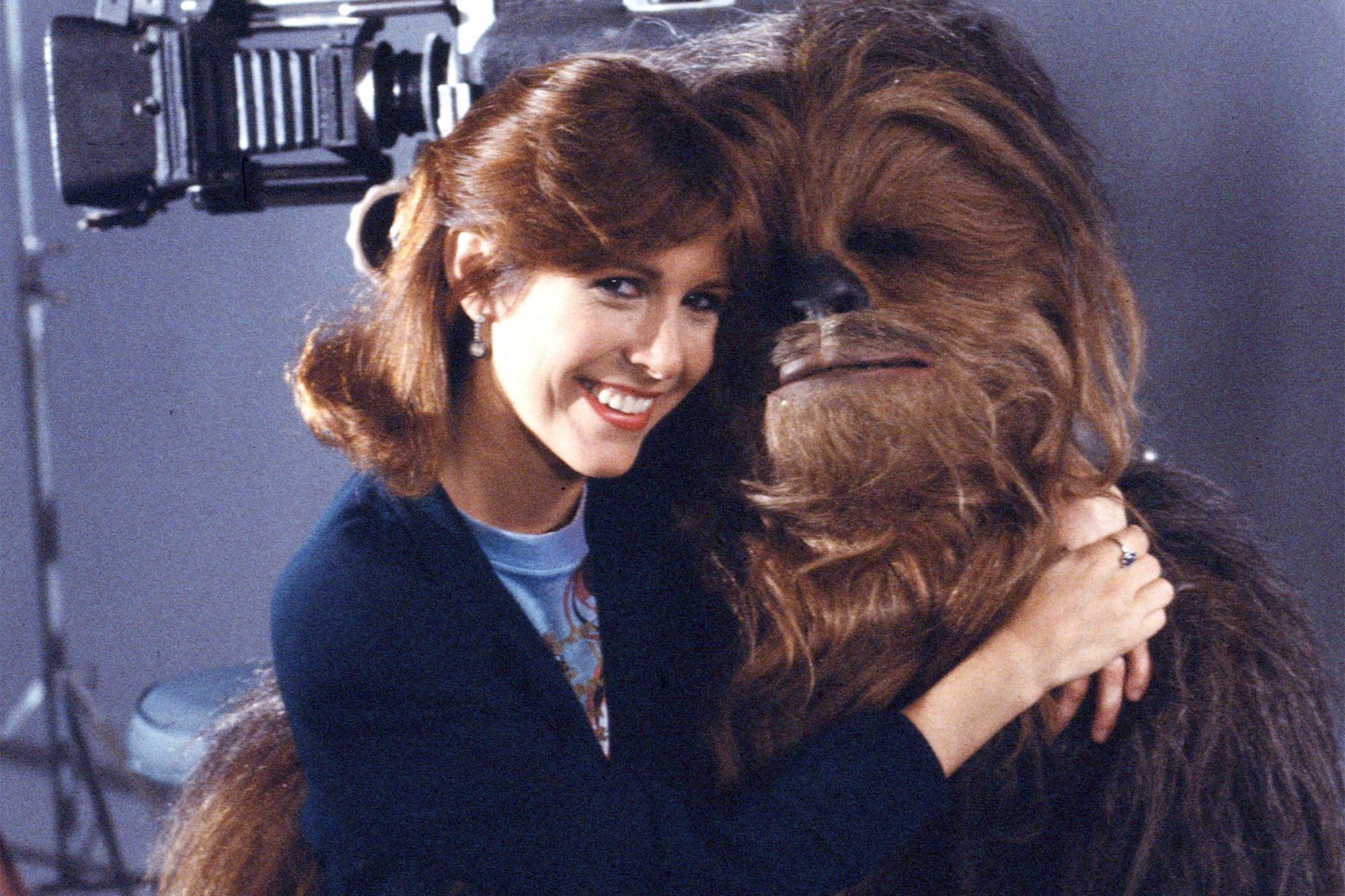 Promotional portrait of American actress Carrie Fisher as she sits on the lap of British actor Peter Mayhew, in costume as Chewbacca, on the set of 'Classic Creatures: Return of the Jedi' (directed by Robert Guenette), a documentary about the second film in the Star Wars saga that focuses on variety of unusual beings that populate the film's world; the program was originally broadcast on November 21, 1983. (Photo by CBS Photo Archive/Hulton Archive)