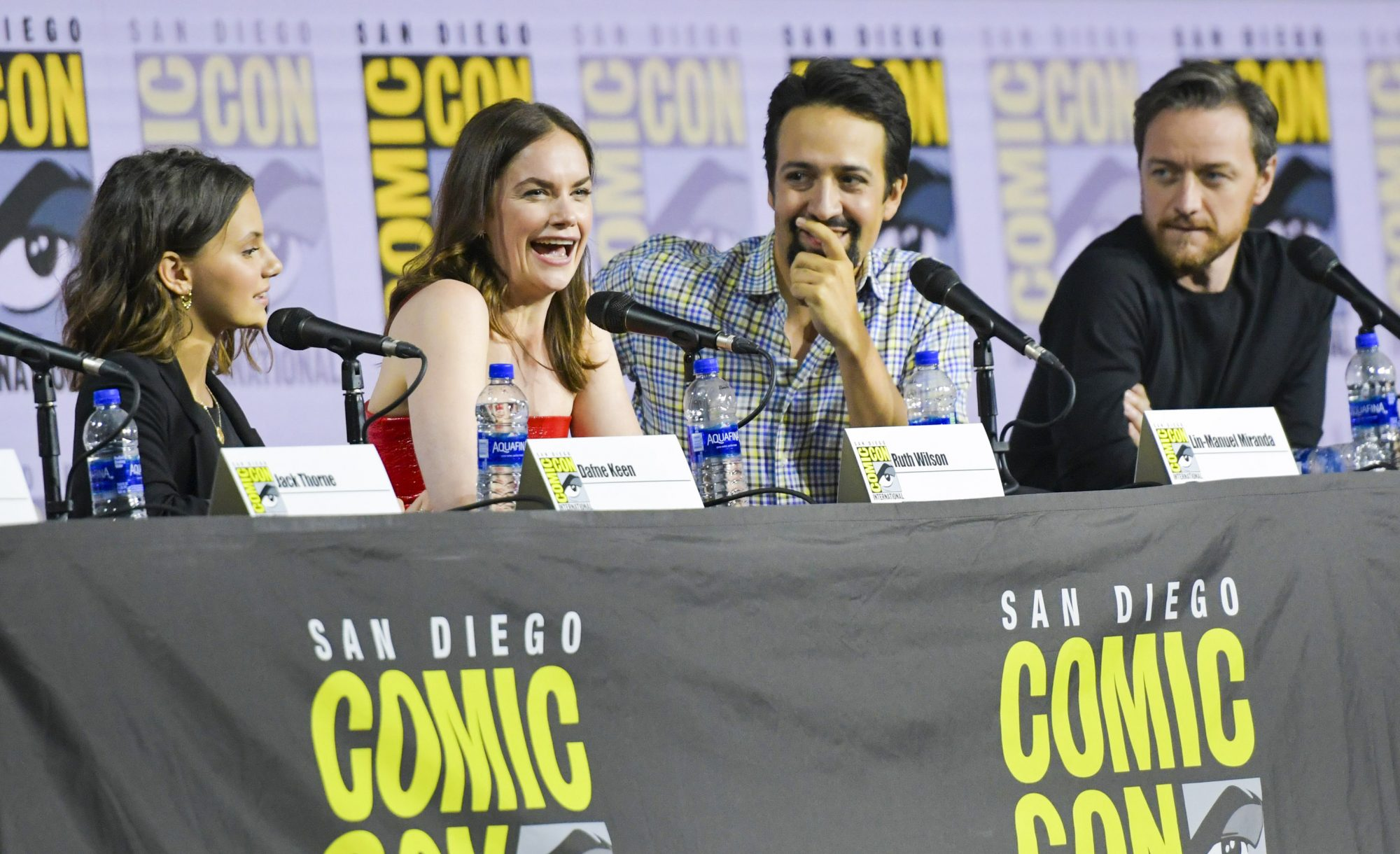 """(L-R) Actors Dafne Keen, Ruth Wilson, Lin-Manuel Miranda and James McAvoy speak during the """"His Dark Materials"""" panel in Hall H during Comic Con in San Diego, California on July 18, 2019. (Photo by Chris Delmas / AFP) (Photo credit should read CHRIS DELMAS/AFP/Getty Images)"""