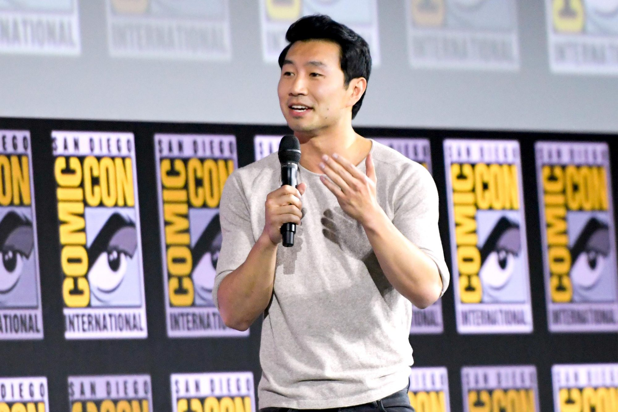 Canadian actor Simu Liu speaks on stage for the Marvel panel in Hall H of the Convention Center during Comic Con in San Diego, California on July 20, 2019. (Photo by Chris Delmas / AFP) (Photo credit should read CHRIS DELMAS/AFP/Getty Images)