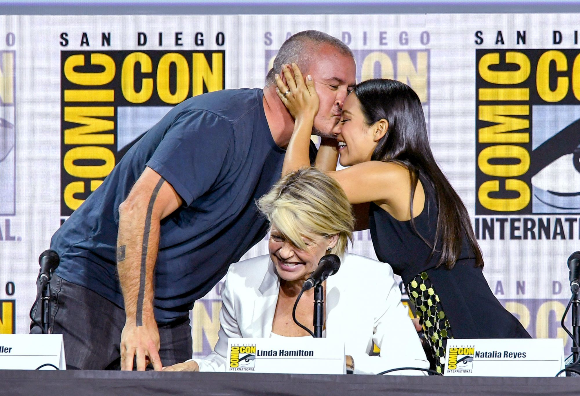 """SAN DIEGO, CALIFORNIA - JULY 18: (L-R) Tim Miller, Linda Hamilton, and Natalia Reyes speak at the """"Terminator: Dark Fate"""" panel during 2019 Comic-Con International at San Diego Convention Center on July 18, 2019 in San Diego, California. (Photo by Kevin Winter/Getty Images)"""