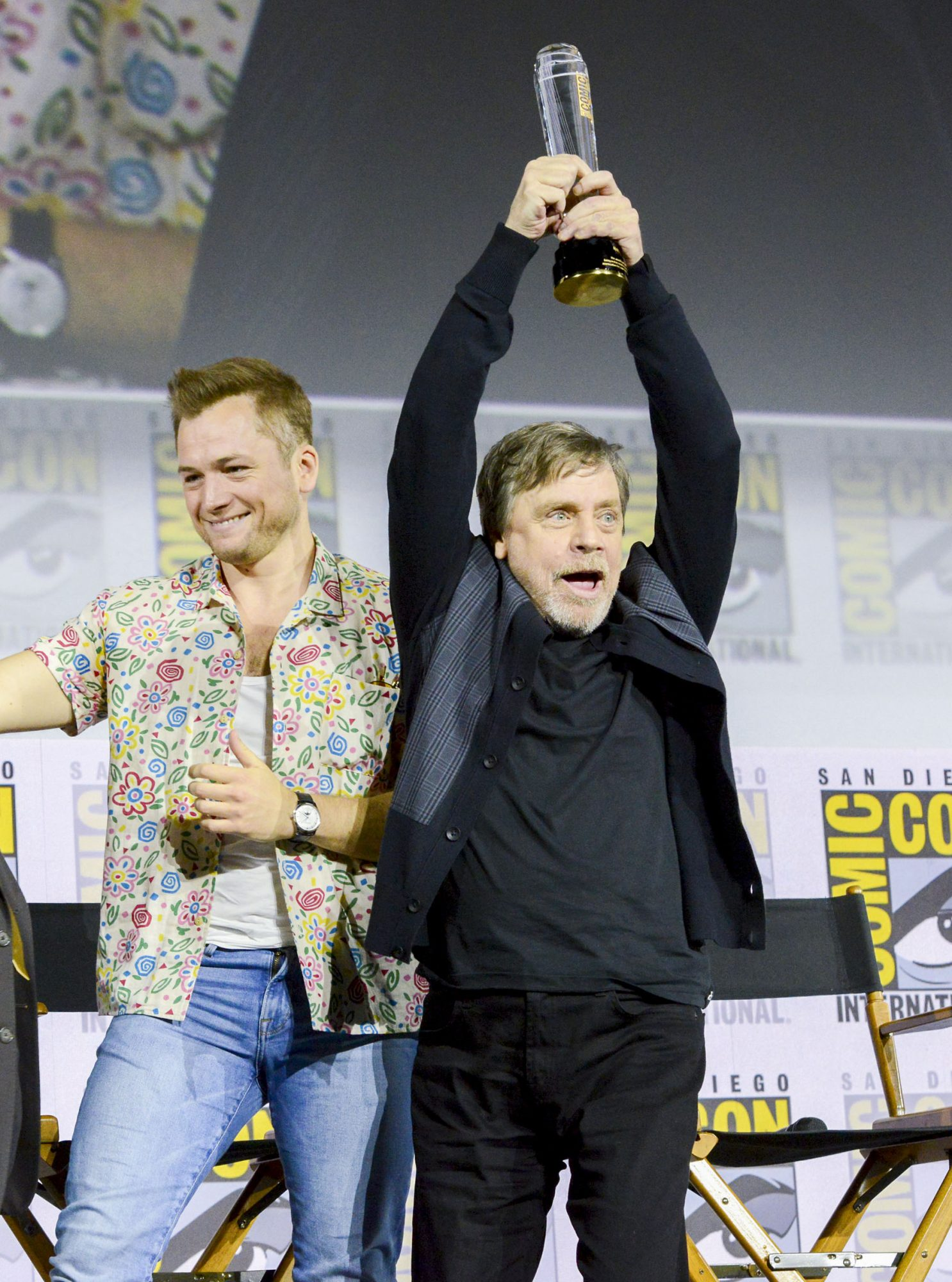 """SAN DIEGO, CALIFORNIA - JULY 19: Taron Egerton and Mark Hamill speak at the Netflix's """"The Dark Crystal: Age Of Resistance"""" Panel during 2019 Comic-Con International at San Diego Convention Center on July 19, 2019 in San Diego, California. (Photo by Albert L. Ortega/Getty Images)"""