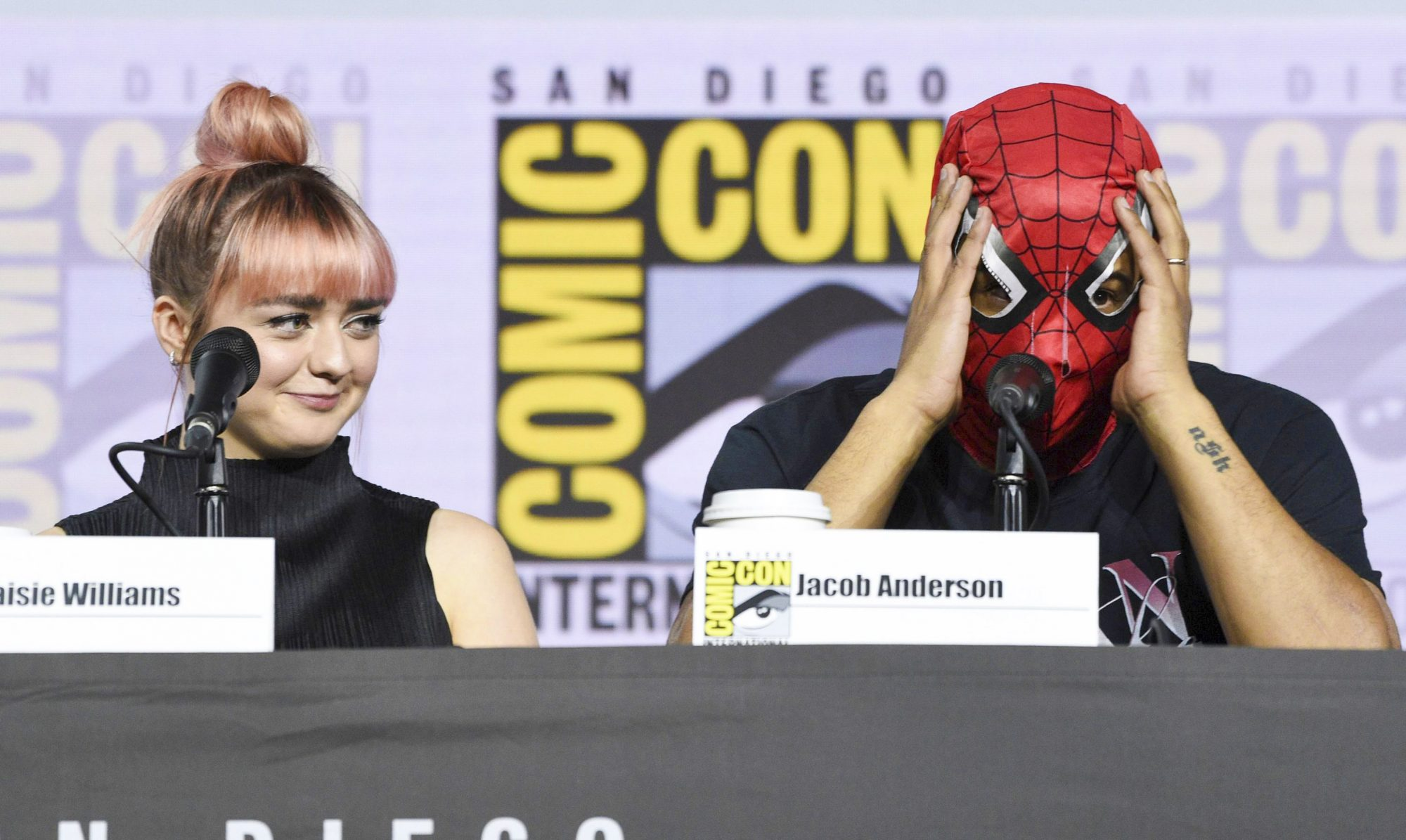 """Mandatory Credit: Photo by Chris Pizzello/Invision/AP/Shutterstock (10342099j) Maisie Williams, Jacob Anderson. Maisie Williams, left, looks at Jacob Anderson as he puts on a Spider-Man mask during the """"Game of Thrones"""" panel on day two of Comic-Con International, in San Diego 2019 Comic-Con - """"Game of Thrones"""" Panel, San Diego, USA - 19 Jul 2019"""