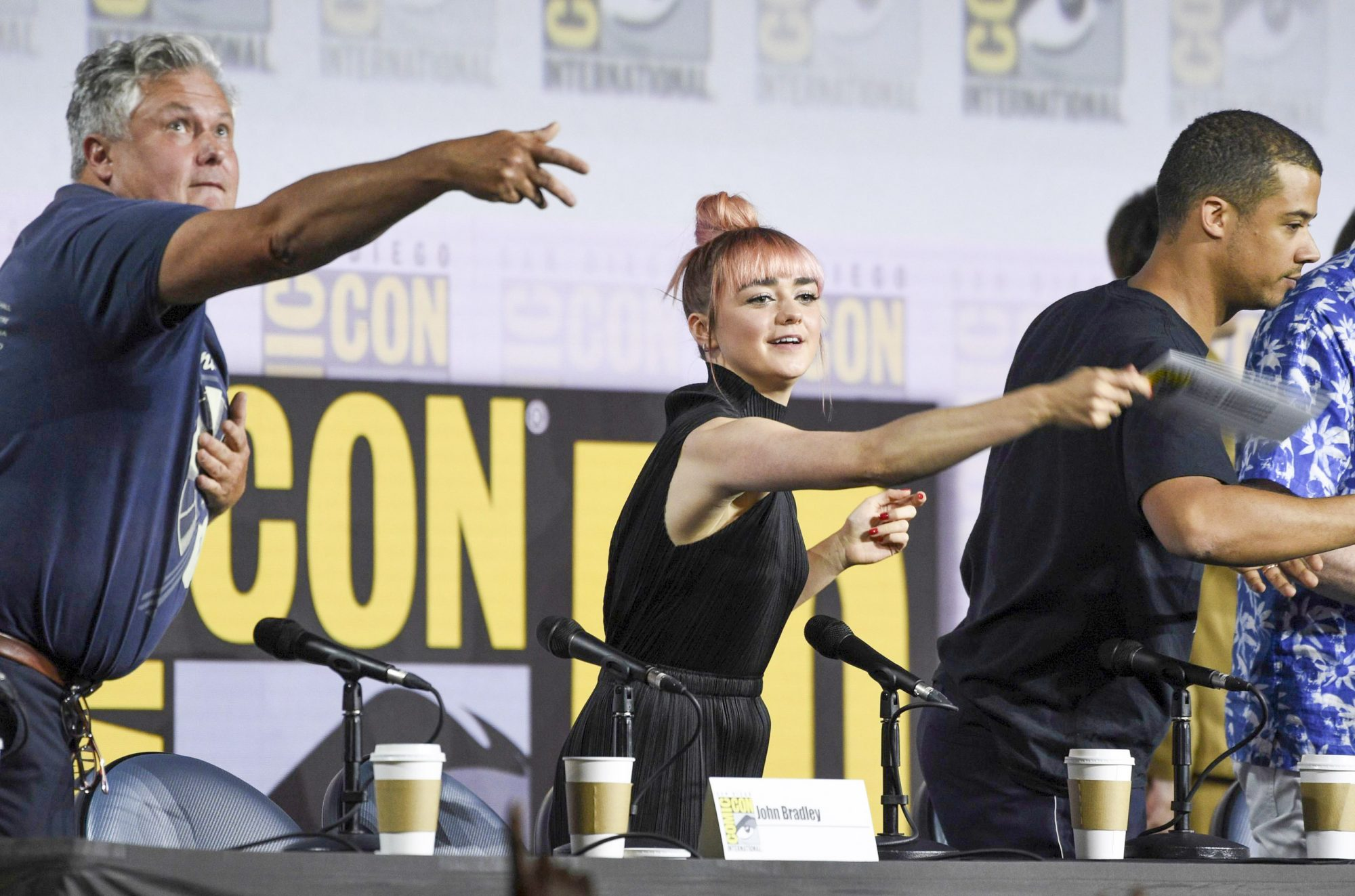 """Mandatory Credit: Photo by Chris Pizzello/Invision/AP/Shutterstock (10342099k) Conleth Hill, Maisie Williams, Jacob Anderson. Conleth Hill, from left, Maisie Williams and Jacob Anderson throw their name card to the audience at the conclusion of the """"Game of Thrones"""" panel on day two of Comic-Con International, in San Diego 2019 Comic-Con - """"Game of Thrones"""" Panel, San Diego, USA - 19 Jul 2019"""