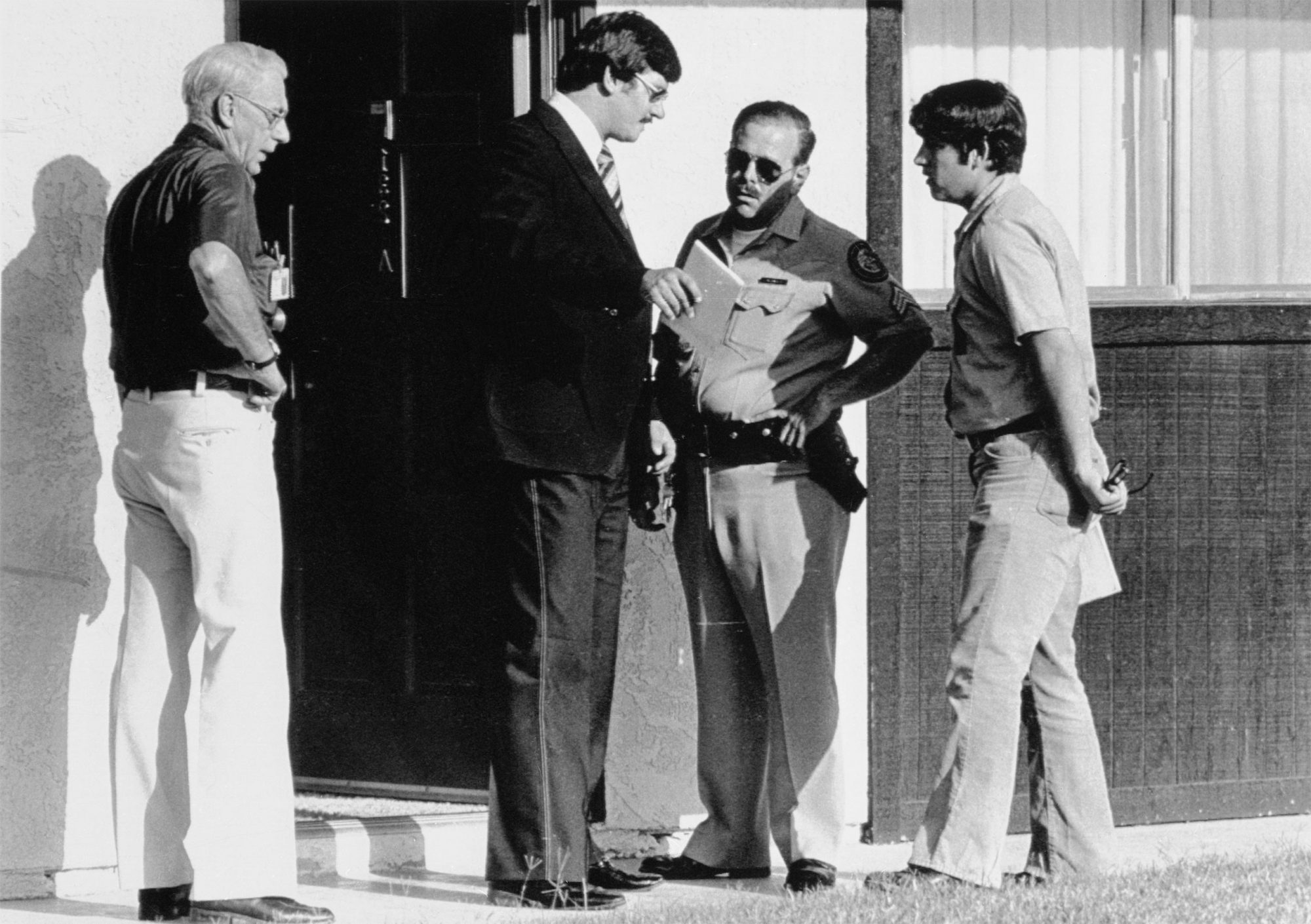 (Original Caption) Scotsdale, Arizona: Police gather outside the apartment where actor Bob Crane was beat to death 6/29. Crane, star of the old TV series Hogan's Heroe's apparently was attacked in his sleep in the early morning hours and hit on the head with a heavy instrument.