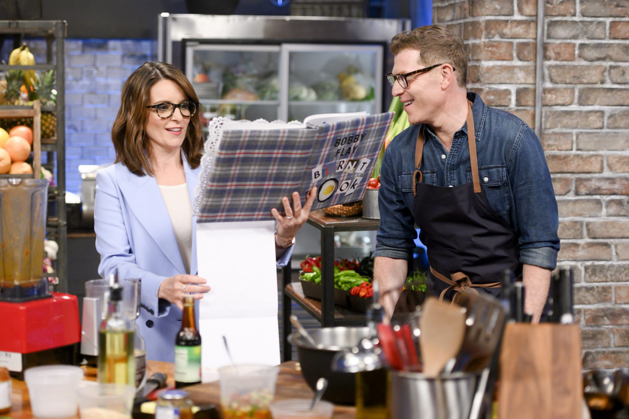 Co-host Tina Fey reads to host Bobby Flay from a burn book as he races to finish his lamb shawarma dish, as seen on Beat Bobby Flay, Season 25.